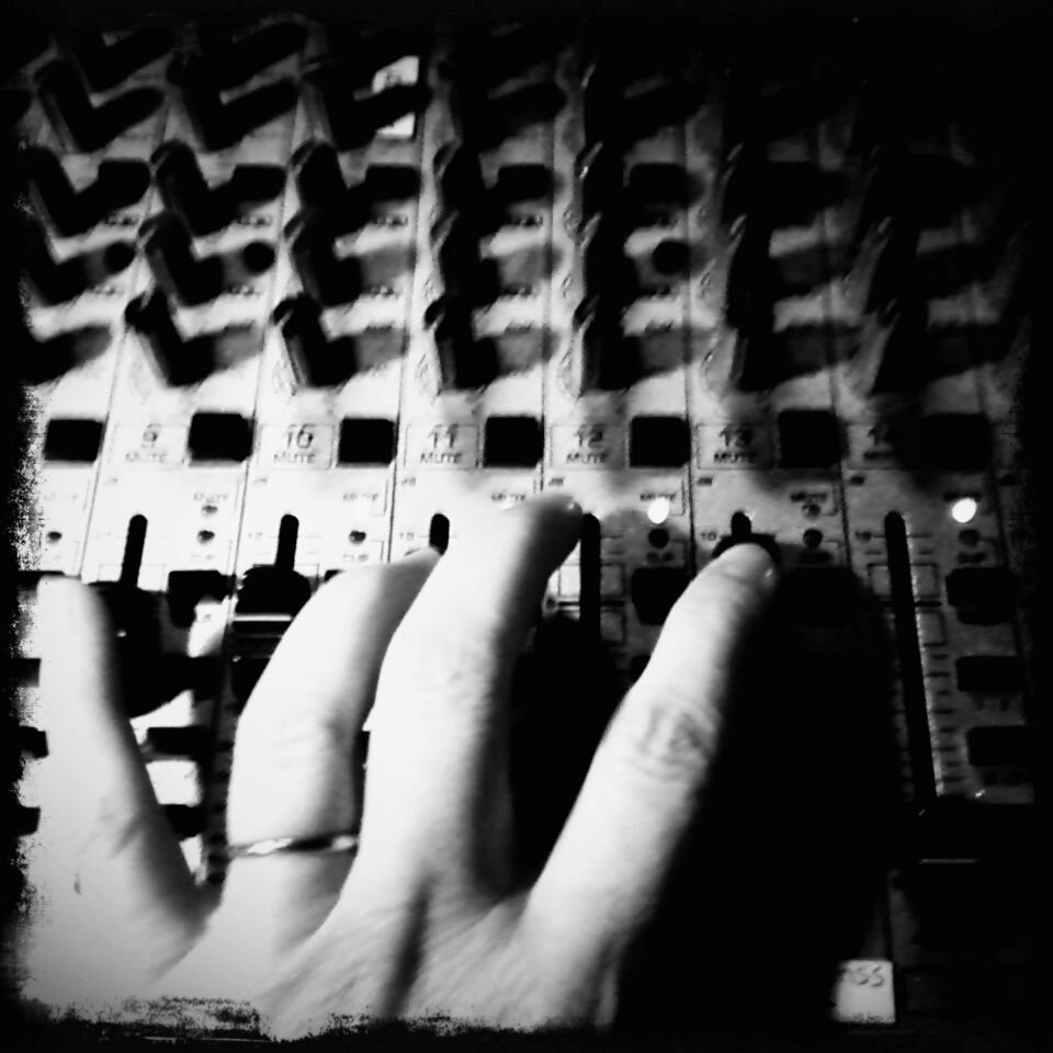 hand on control panel of a sound-booth