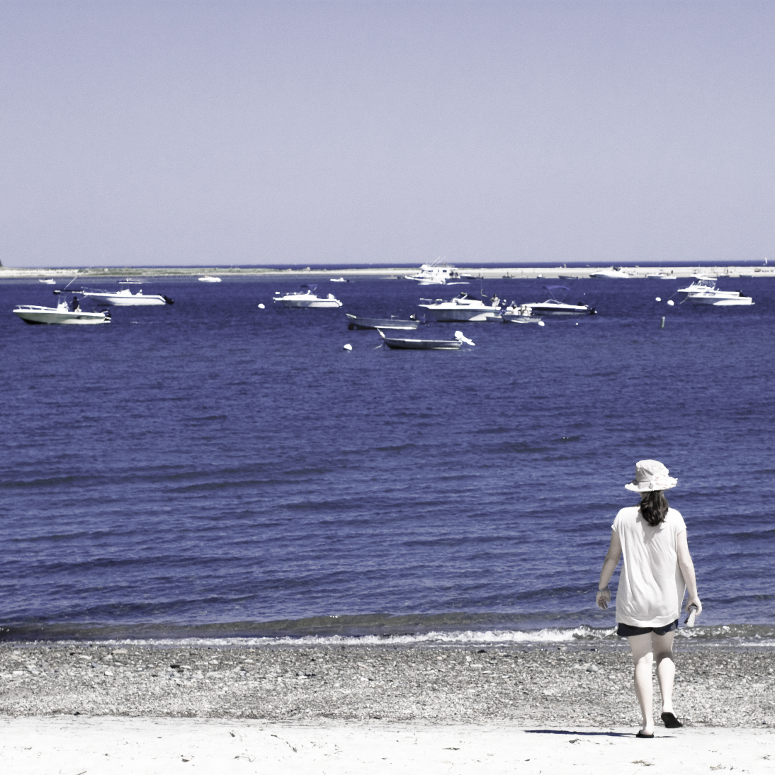 young woman walking on a beach with moored boats in the bay
