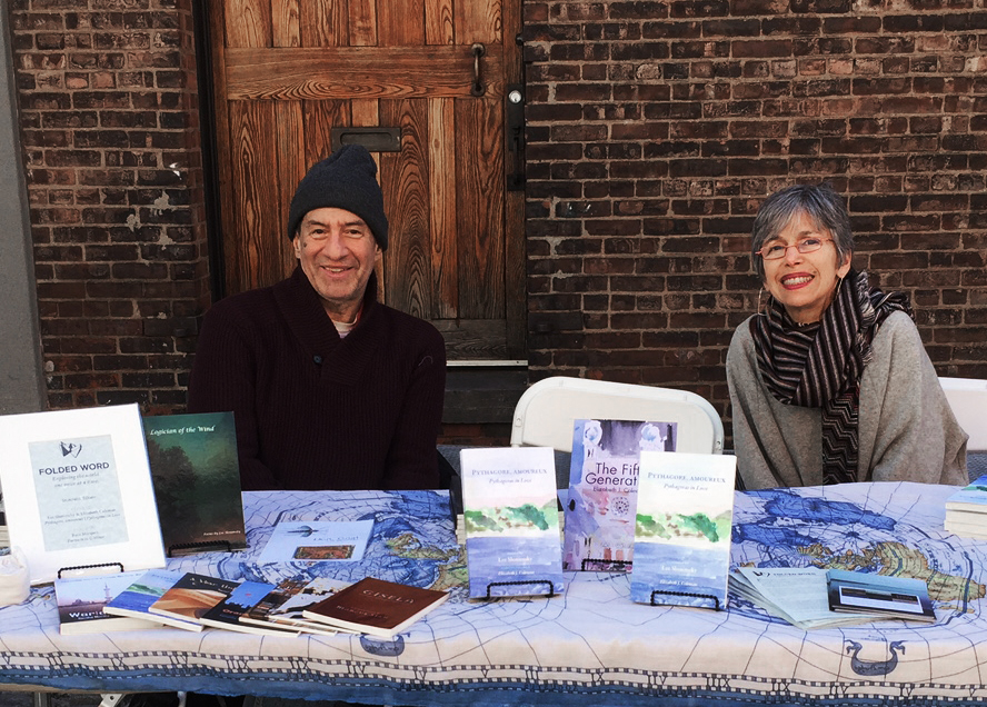 two people with hats and coats sitting at a table with books
