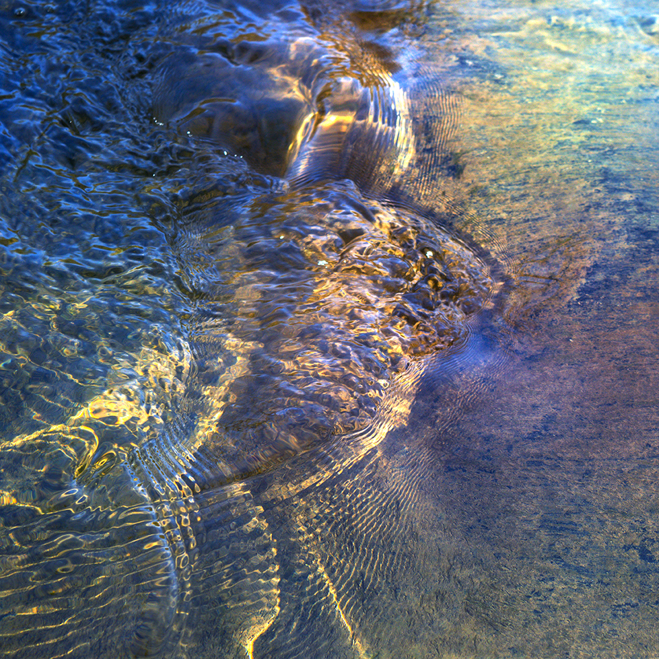 colorized ripples on a stream surface