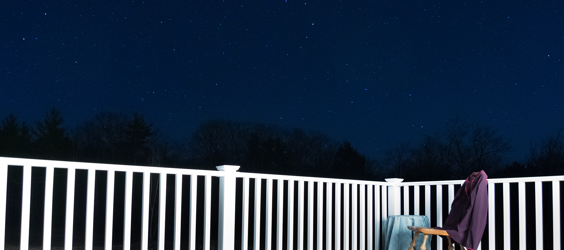 empty chair on deck looking up at stars